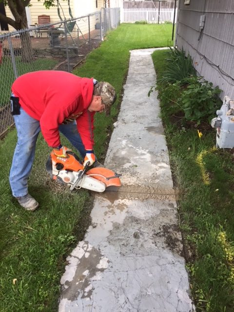 A plumber cutting a side walk for demolition before a water line repair.