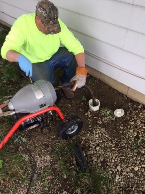 A plumber cleaning a sewer line