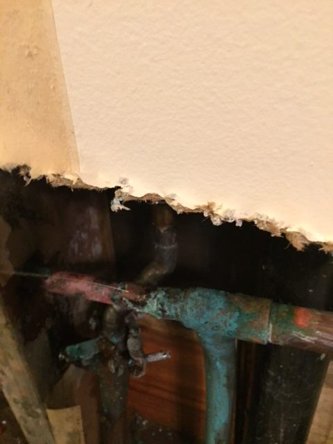 A leaking, rusted pipe before repair