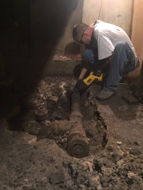 a plumber beginning demo before installing a back water valve