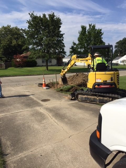 Construction equipment digging to install a new service line.