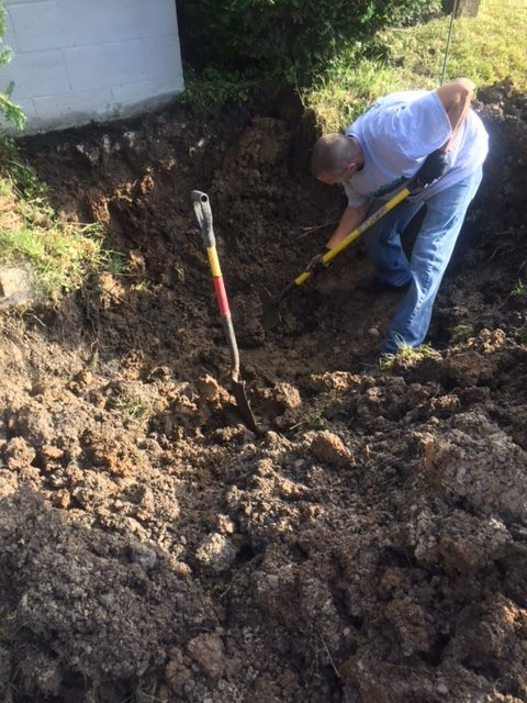 A plumber digging to locate a water main leak.